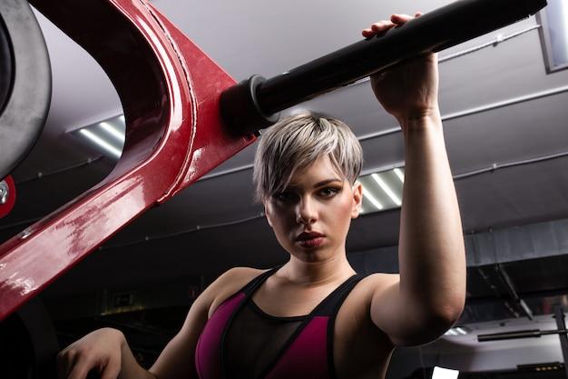 Menina bonita esporte está envolvida em um simulador no ginásio. menina bonita com a bela figura apertada. garota fitness no ginásio