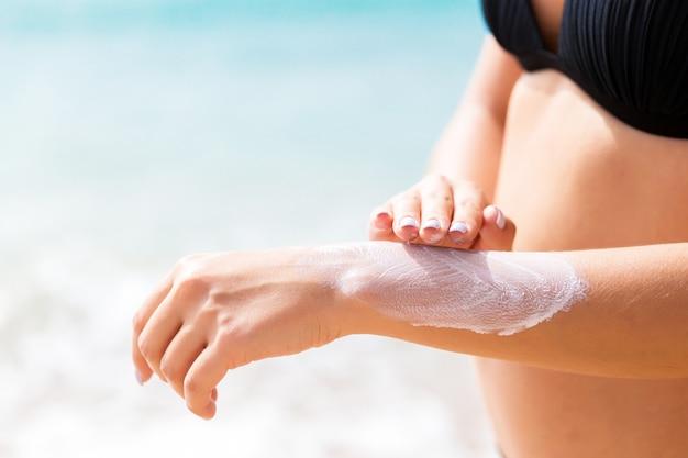Menina bonita está colocando loção de sol na mão na praia