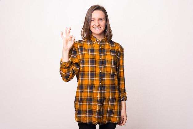Menina bonita está de pé sobre um fundo branco, sorrindo para a câmera e mostrando um gesto ok.