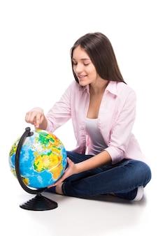 Menina bonita está sentada no chão e olhando para o globo.