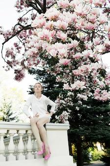 Menina bonita está sentado no parapeito sob a incrível árvore de magnólia