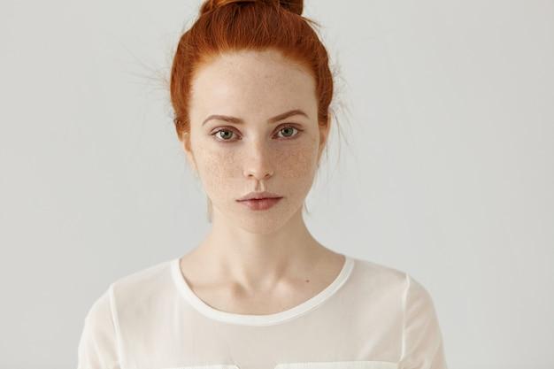 Menina bonita estudante com cabelo ruivo no nó relaxando em casa depois da faculdade. tiro na cabeça da concurso jovem encantadora com sardas vestindo blusa branca posando
