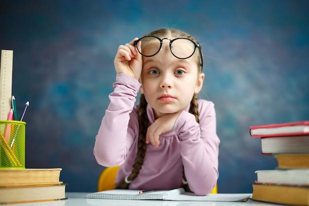 Menina bonita estudante primário com óculos