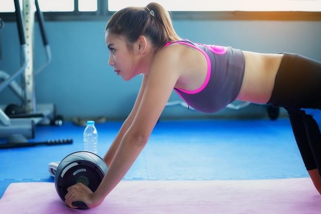 Menina bonita exerce o abdômen com a roda para fortalecer os músculos no público gy