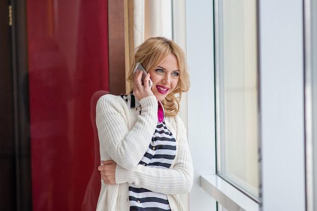 Menina bonita falando ao telefone perto de uma janela, loira