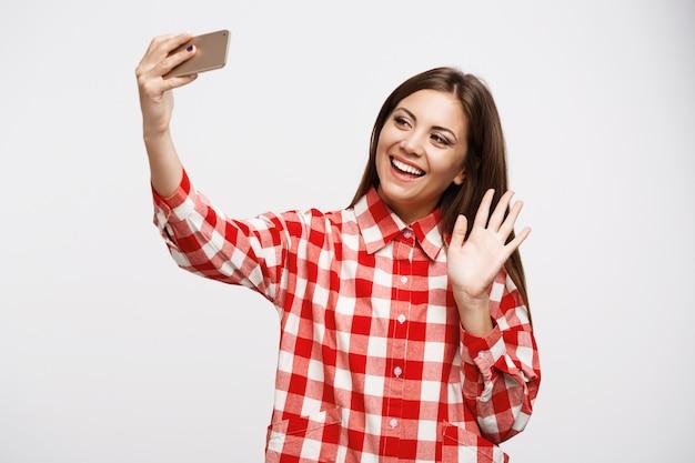 Menina bonita, fazendo chamadas de vídeo com os amigos, acenando com a mão esquerda