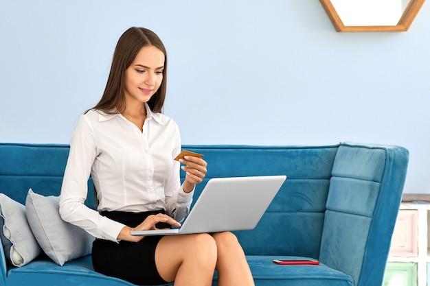 Menina bonita fazendo compras on-line e usando cartão de crédito