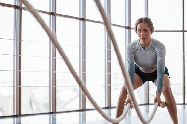 Menina bonita fazendo crossfit. jovem esportiva fazendo exercícios na academia pela manhã