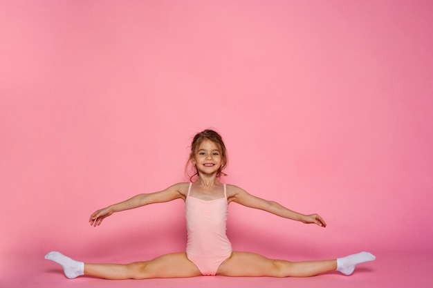 Menina bonita fazendo ginástica com uma malha no fundo rosa