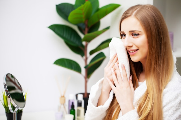 Menina bonita, fazendo o procedimento de cuidados faciais no banheiro