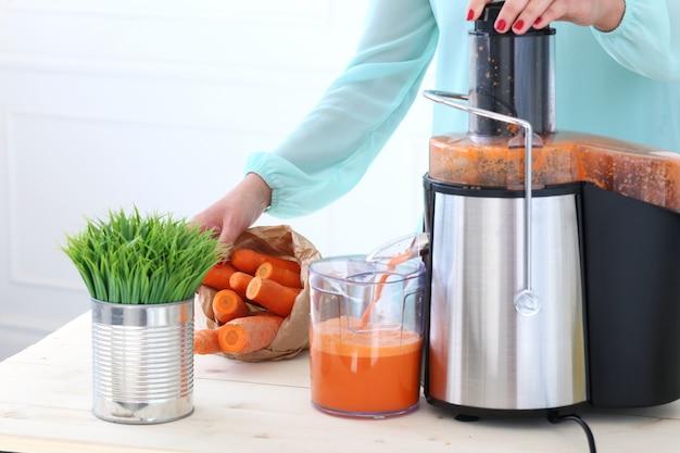 Menina bonita fazendo suco de cenoura