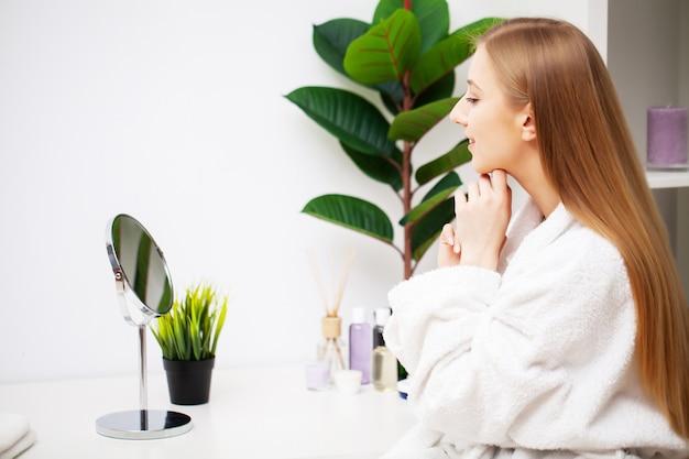 Menina bonita fazendo tratamentos faciais cuidados no banheiro
