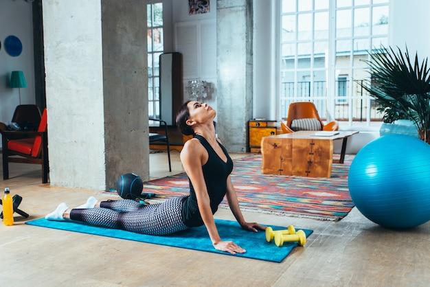 Menina bonita, fazendo treinamento e yoga em casa pela manhã