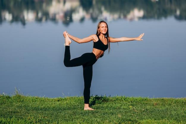 Menina bonita fazendo yoga asana e segura pela mão a perna nas costas.