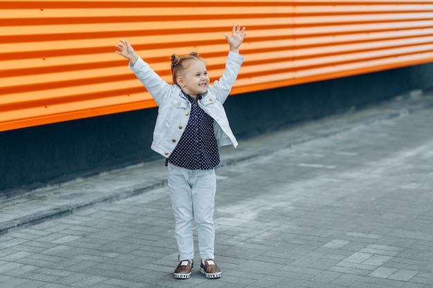 Menina bonita feliz com as mãos levantadas sorrindo e rindo