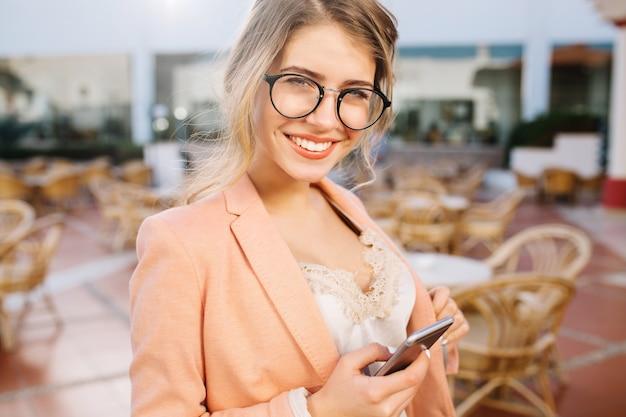 Menina bonita feliz com smartphone cinza na mão, sorridente, estudante, mulher de negócios. café de rua, terraço. usando óculos elegantes, jaqueta rosa, blusa de renda bege.