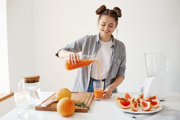 Menina bonita feliz derramando batido de desintoxicação de toranja em vidro sorrindo sobre parede branca. nutrição dieta saudável.