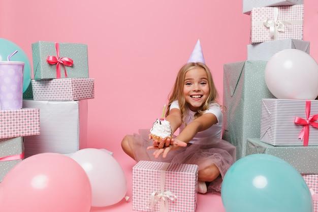 Menina bonita feliz em um chapéu de aniversário comemorando