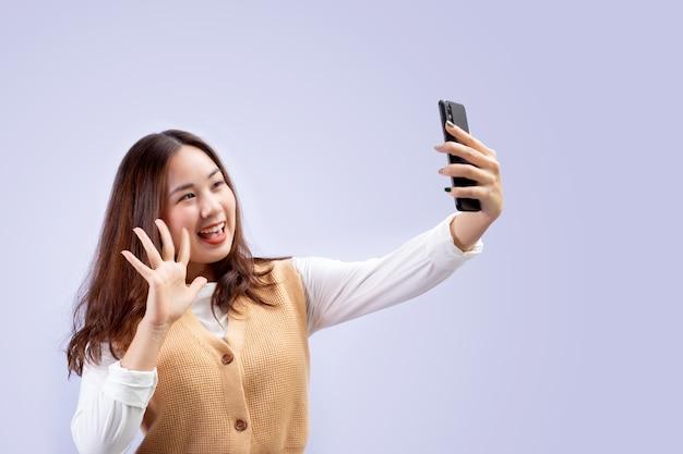 Menina bonita feliz fazendo autorretrato no smartphone sobre fundo cinza