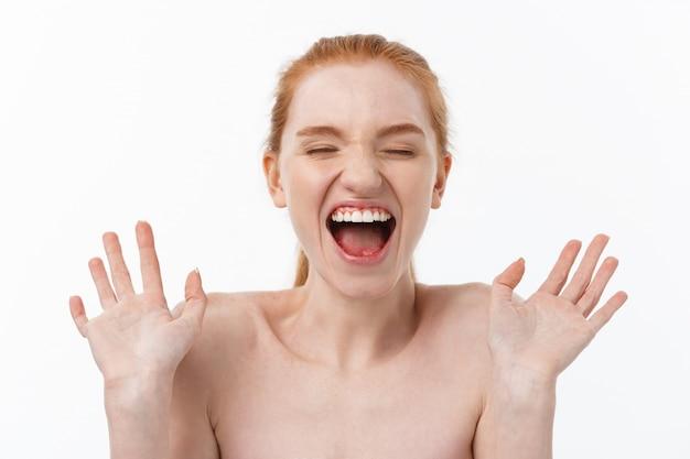 Menina bonita feliz segurando suas bochechas com uma risada, olhando para o lado. expressões faciais expressivas. cosmetologia e spa.