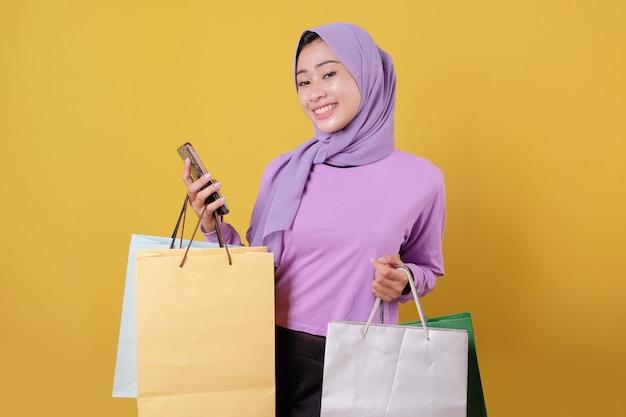 Menina bonita feliz sorridente usando celular, compras online, trazer uma bolsa, alegre