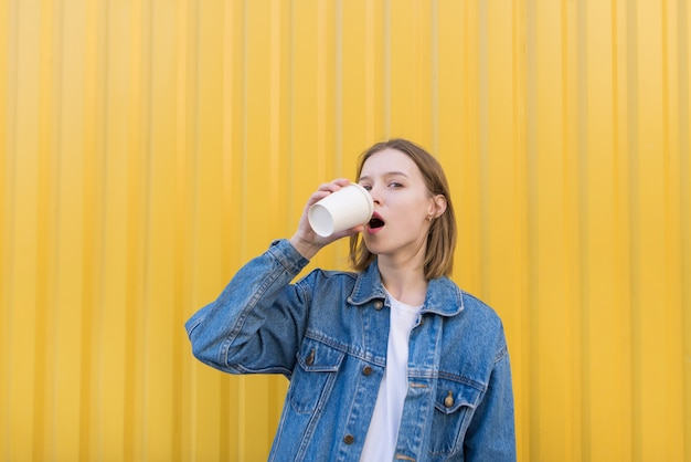 Menina bonita fica no fundo da parede amarela e bebe café da xícara.