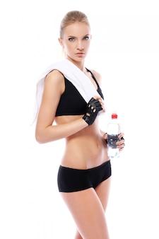 Menina bonita fitness com toalha e garrafa de água