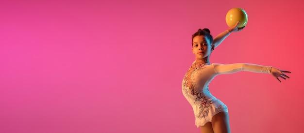 Menina bonita ginasta rítmica afro-americana praticando na parede gradiente com luz de néon