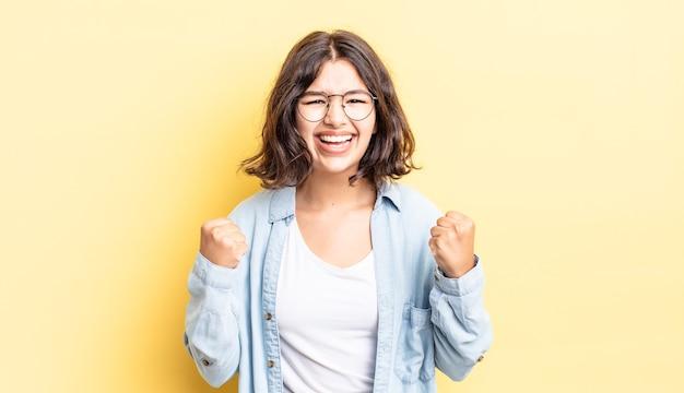 Menina bonita gritando triunfantemente, rindo e se sentindo feliz e animada enquanto celebra o sucesso