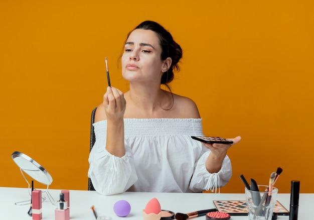 Menina bonita irritada se senta à mesa com ferramentas de maquiagem olha para o pincel de maquiagem segurando a paleta de sombras isolada na parede laranja