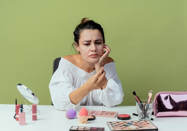 Menina bonita irritada se senta à mesa com ferramentas de maquiagem segura e olha para o pincel de maquiagem isolado na parede verde