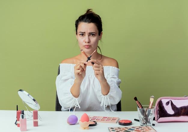 Menina bonita irritada sentada à mesa com ferramentas de maquiagem cruzando pincéis de maquiagem gesticulando não isolado na parede verde