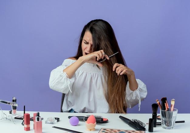 Menina bonita irritada sentada à mesa com ferramentas de maquiagem finge cortar o cabelo com uma tesoura isolada na parede roxa