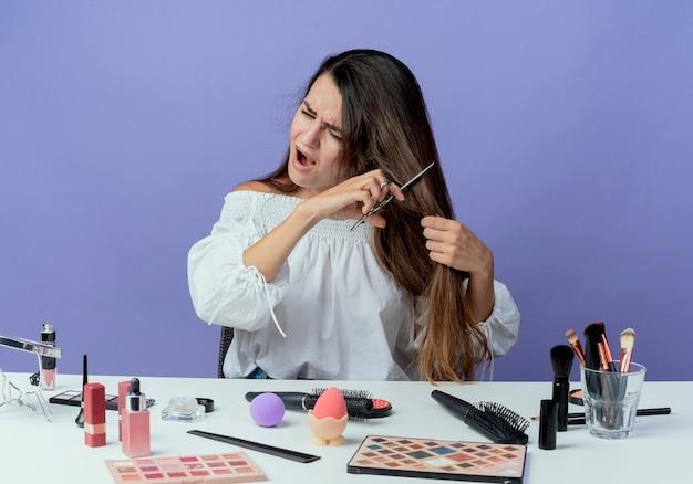 Menina bonita irritada sentada à mesa com ferramentas de maquiagem finge cortar o cabelo com uma tesoura olhando para o lado isolado na parede roxa