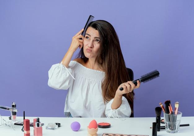Menina bonita irritada sentada à mesa com ferramentas de maquiagem segurando pentes de cabelo olhando para cima, isolados na parede roxa