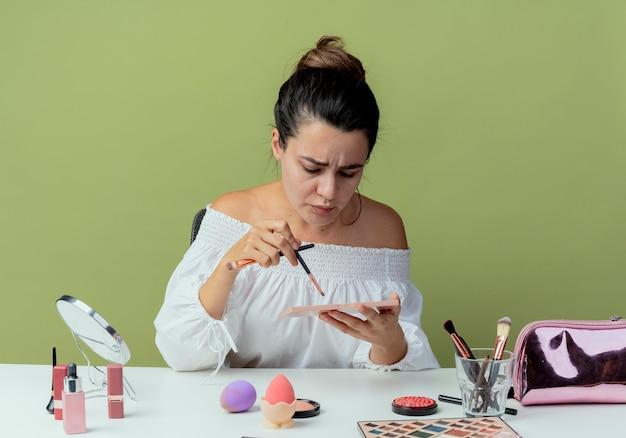 Menina bonita irritada sentada com os olhos fechados à mesa com ferramentas de maquiagem segurando e olhando para a paleta de sombra e o pincel de maquiagem isolado na parede verde