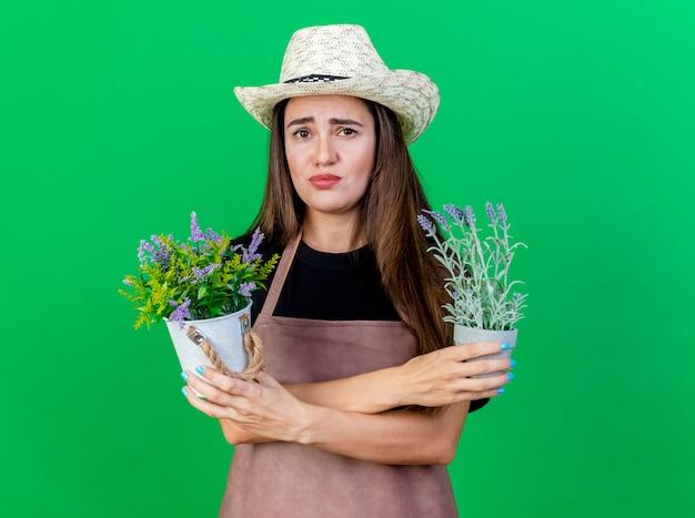 Menina bonita jardineira preocupada de uniforme, usando chapéu de jardinagem, segurando e cruzando flores em um vaso de flores isolado no fundo verde