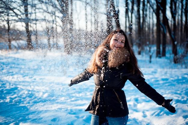 Menina bonita joga neve em um parque de inverno