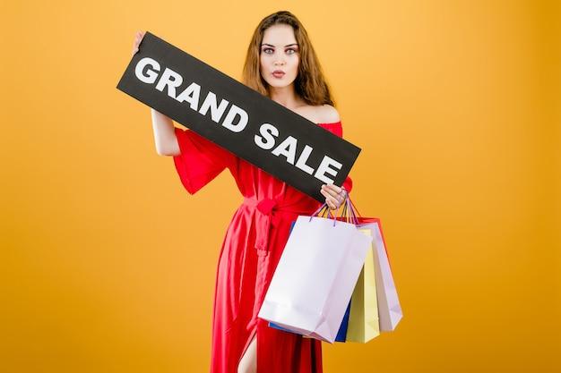 Menina bonita jovem animada tem sinal de grande venda com sacolas coloridas isoladas sobre amarelo