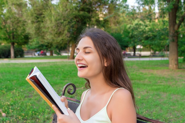 Menina bonita jovem brownhair cheira um livro impresso fresco sentado no banco no parque