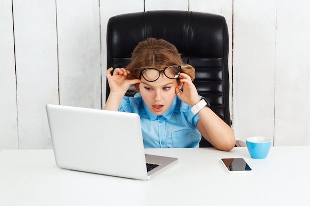 Menina bonita jovem cansada, sentado no local de trabalho no escritório.