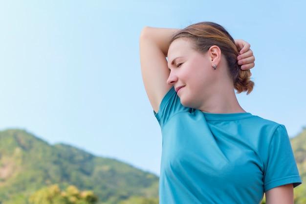 Menina bonita, jovem cheirando, apreciando o frescor de suas axilas limpas, sorrindo. bom desodorante, antitranspirante. caminhar ao ar livre nas montanhas, pessoa feliz respirando ar fresco