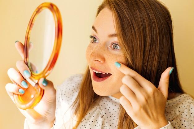Menina bonita jovem chocada com sardas no rosto