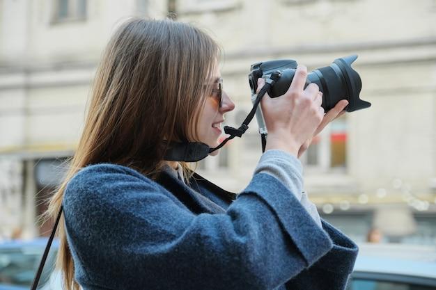 Menina bonita jovem com câmera na cidade de primavera
