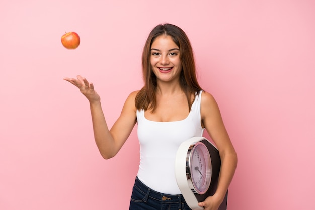 Menina bonita jovem com máquina de pesagem e com um fundo de maçã
