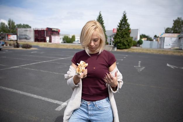 Menina bonita jovem comendo cachorro-quente no estacionamento.