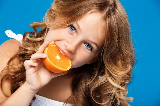 Menina bonita jovem comendo laranja sobre parede azul