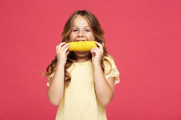 Menina bonita jovem comendo milho na parede rosa
