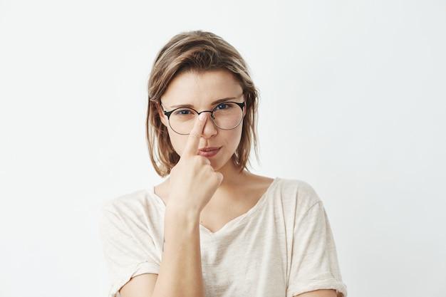 Menina bonita jovem, corrigindo os óculos.