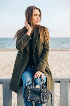 Menina bonita jovem de casaco verde com uma bolsa